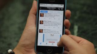 """Phone held in hands - tweets by Robert Penner are visible, including """"I repeatedly asked Nepal Police to tell me under what charges they're taking me but they won't say"""" and """"Nepal Immigration says they're holding me overnight"""""""
