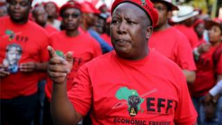 Leader of South Africa's left-wing Economic Freedom Fighters (EFF) Julius Malema gestures after arriving at the Johannesburg Stock Exchange (JSE) in Sandton
