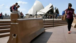 Tourists walk past bollards at the Sydney Opera House designed to shield against vehicle attacks