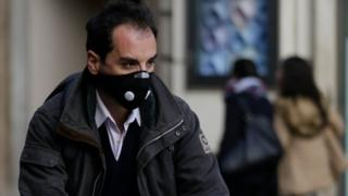 A cyclist wears a protective mask as he pedals in downtown Rome. 24 December 2015.