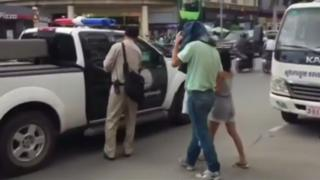 Video footage showing a covered Clive Cressy being led out to a police car in Cambodia