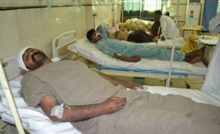 Pakistani men rest in hospital after an attack on a Sufi shrine