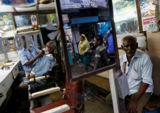 A man gets a shave inside a barber shop at a slum in Mumbai, India, August 3, 2016