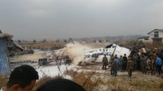 Photo of rescuers by the crashed plane