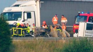Firefighters and rescuers stand next to the wreckage of a van after it collided with a barricade made with tree trunks set up by migrants on the A16 highway near Guemps, northern France, on 20 June