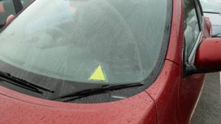A picture of the yellow triangle on a car window to alert emergency teams to a driver's medical advice