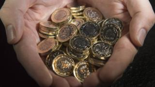 New pound coins in a hand