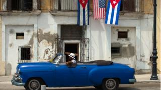An old car passes by a house decorated with American and Cuban flags in Havana, Cuba (20 March 2016)