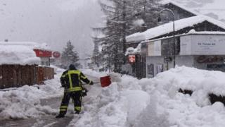 Workers remove snow beside the Zermatt train station after heavy snowfall and avalanches trapped more than 13,000 tourists at Zermatt, 9 January