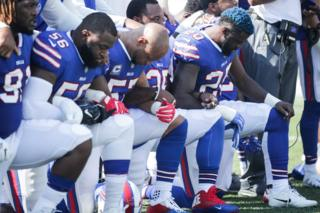 Buffalo Bills players kneel during the American National anthem before an NFL game against the Denver Broncos, 24 September 2017