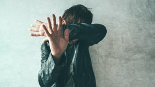 Man covering face with arms