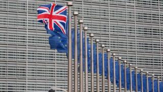 A Union Jack flag flies next to European Union flags