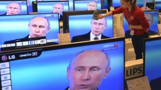 Woman dusts TVs in shop, with Putin on screen