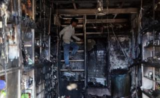 A person inspects a pharmacy store after a fire broke out, in Mumbai, India, 30 June 2016