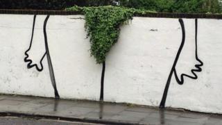 Un graffiti en una pared muestra la silueta de unas piernas con un pequeño arbusto