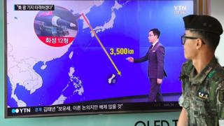 South Korean soldier walks past TV showing a graphic of the distance between North Korea and Guam at a railway station in Seoul on 9 August 2017