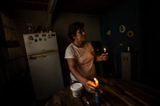 An older woman lights a candle