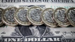 Row of new pound coins on one dollar bill