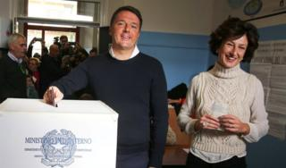 Italian Prime Minister Matteo Renzi casts his vote for the referendum on constitutional reform as he is flanked by his wife Agnese, in Pontassieve, near Florence, northern Italy December 4, 2016
