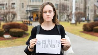 Violet Massie holding up a sign reading 'Me Next?'