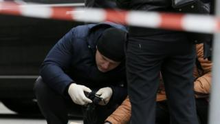 Police investigate the scene of the attack outside the Premier Palace hotel in Kiev