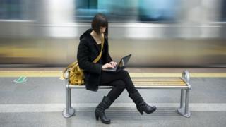 امرأة تستخدم حاسبا محمولا