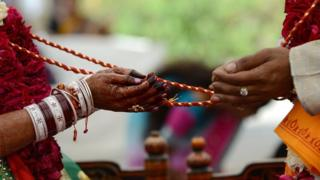 An Indian bridal couple participate in Hindu rituals during a mass marriage