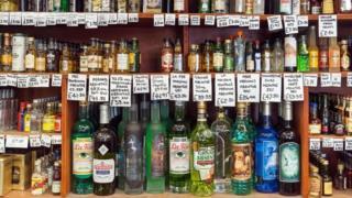 Botellas de diferentes tipos de alcohol en unas repisas