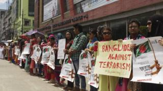 Bangladeshi students and teachers hold placards as they form a human chain to protest terrorism in Dhaka on August 1, 2016