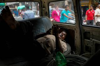 An Indian labourer rests inside his van in the old quarters of New Delhi