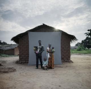 A family stand in front of their house.