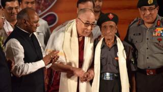 In this photograph taken on 2 April 2017, Tibetan spiritual leader the Dalai Lama (L) shakes hands with retired Assam Rifles personnel Naren Chandra Das