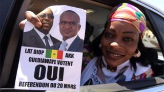 """A woman in a car holds a """"yes"""" sign on 12 March, 2016 in Guediawaye suburb in Dakar, during the campaign for referendum on revising Senegal""""s constitution, including reducing the presidential mandate from seven to five years."""