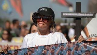 Relatives of police officers hold crosses as they protest about the death of 91 members of the security forces since the beginning of 2017 at Copacabana beach, in Rio de Janeiro, Brazil, on July 23, 2017