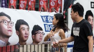Pedestrians walk past a banner for new party Youngspiration showing disqualified candidate Edward Leung (L) and Baggio Leung (C) during the Legislative Council election in Hong Kong on September 4, 2016