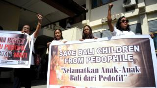 Activists display banners against paedophilia in front of a holding cell where Australian Robert Andrew Fiddes Ellis was waiting before attending his trial at a court in Denpasar, on the Indonesian resort island of Bali on July 14, 2016.