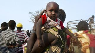 أمرأة تحمل رضيعاً بينما ينتظر اللاجئون من جنوب السودان عربات لتنقلهم من مركز اللاجئين في شمالي أوغندا إلى معسكر خاص للاجئين