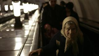 An elderly women rides an escalator in a Moscow metro station.