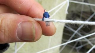 Tiny figures in a web of fabric