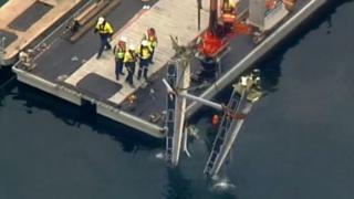 Nhà chức trách dùng cần cẩu để trục với một mảnh thủy phi cơ hôm thứ Năm.