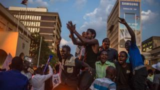 Harare residents celebrate in front of the parliament after the resignation of Zimbabwe's President Robert Mugabe (21 November 2017)