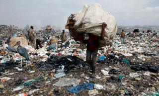 A scavenger carries recyclable plastic materials packed in a sack at the Dandora dumping site on the outskirts of Nairobi, Kenya August 25, 2017. Picture taken August 25, 2017.