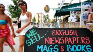 """women in beach clothes walking past a sign that reads """"We sell English newspapers mags and books"""""""