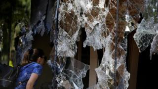 یک روز پس از اعتراضات زنی از شیشه شکسته پنجره به درون ساختمان کنگره نگاه می کند