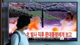 People watch a television broadcast reporting the North Korean missile launch
