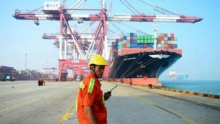 A Chinese worker looks on as a cargo ship is loaded at a port in Qingdao