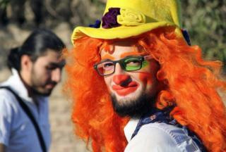 This undated picture from media activist Ahmad al-Khatib shows Syrian social worker Anas al-Basha, 24, dressed as a clown while posing for a photograph in Aleppo, Syria