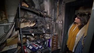 Restaurant owner Shaima Swift examining the damage