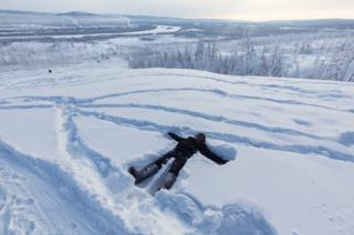 Ayal lays down in the snow on the heights of Verkhoyansk while waiting for his mother and some of her friends to come up the hill. The smoke coming out of the coal power stations of the village can be seen in the background.