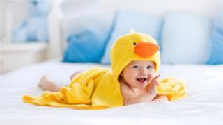 Banyo havlusuna sarılı gülümseyen bebek
